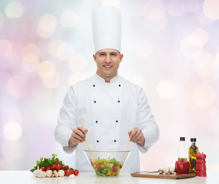 gastronomy: happy male chef cooking vegetable salad over blue lights background Stock Photo