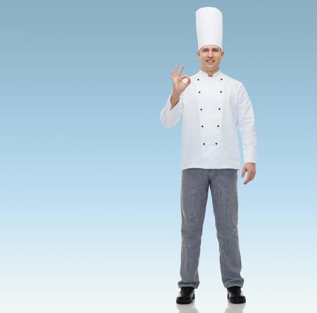 uniforme: Cocinero feliz Cocinero de sexo masculino que muestra el signo ok sobre fondo azul