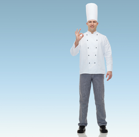 chef kitchen: happy male chef cook showing ok sign over blue background