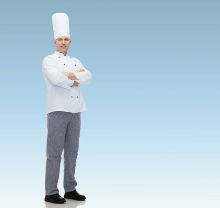mani incrociate: felice cuoco chef di sesso maschile con le mani incrociate su sfondo blu