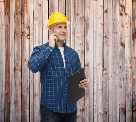 phone calls: smiling male builder or manual worker in helmet with clipboard calling on smartphone over wooden fence background Stock Photo