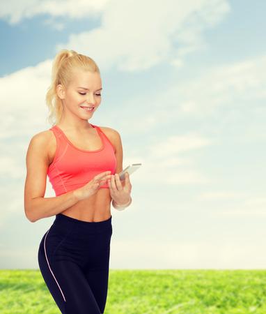 Sorridente donna sportiva con lo smartphone Archivio Fotografico - 45974405