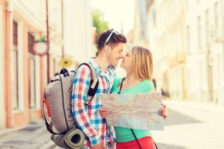 niño con mochila: sonriente pareja con el mapa y la mochila en la ciudad