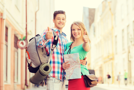 mat like: smiling couple with map and backpack showing thumbs up in city