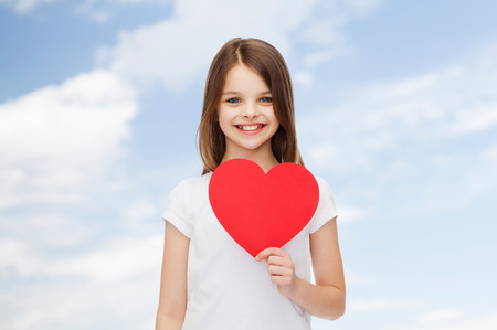 pretty young girl: smiling girl in white t-shirt holding red heart cutout over natural background