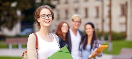 group of happy teenage students with school folders