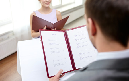 menus: close up of couple with menu choosing dishes at restaurant Stock Photo