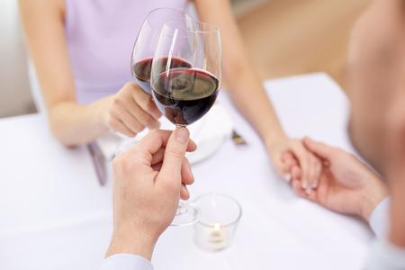 familia cenando: close up de la joven pareja con vasos de vino tinto en el restaurante
