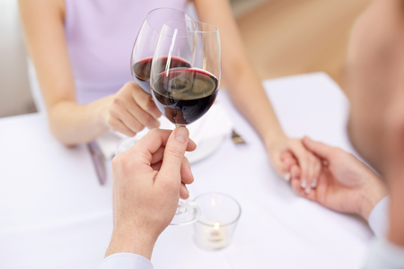 dining: close up of young couple with glasses of red wine at restaurant