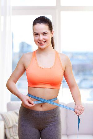 cintura: feliz mujer deportiva que mide su cintura con la cinta en el hogar