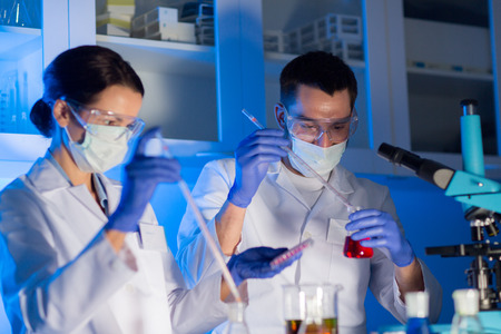 close up of young scientists with pipette and flasks making test or research in clinical laboratory