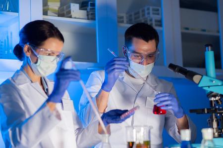 dichten van jonge wetenschappers met een pipet en flacons maken testen of onderzoek in klinisch laboratorium
