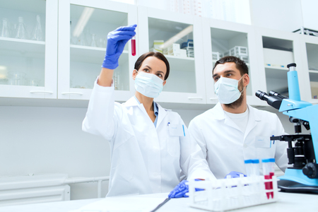 clinical laboratory: young scientists with test tube and microscope making research in clinical laboratory