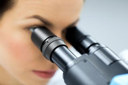 close-up van jonge vrouwelijke wetenschapper gezicht op zoek naar oculair microscoop en het maken van of onderzoek in klinisch laboratorium