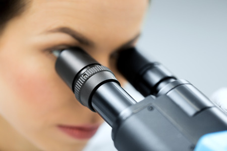 close up of young female scientist face looking to microscope eyepiece and making or research in clinical laboratory