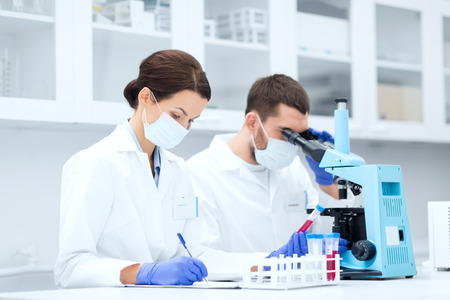 pharmacy equipment: young scientists with test tube and microscope making research in clinical laboratory and taking notes Stock Photo
