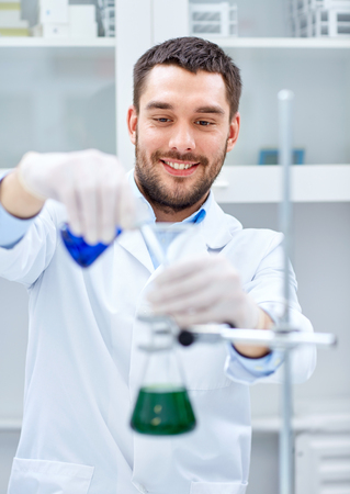 reagents: young scientist mixing reagents from glass flasks and making test or research in clinical laboratory