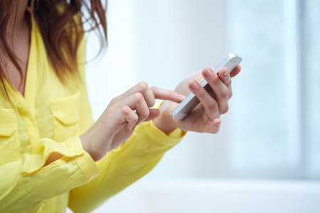 check room: close up of teenage girl hands with smartphone at home