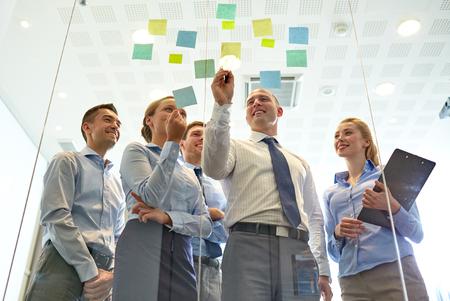 Affari, la gente, il lavoro di squadra e il concetto di pianificazione - sorridente business team con l'indicatore e adesivi che lavorano in ufficio Archivio Fotografico - 45978826