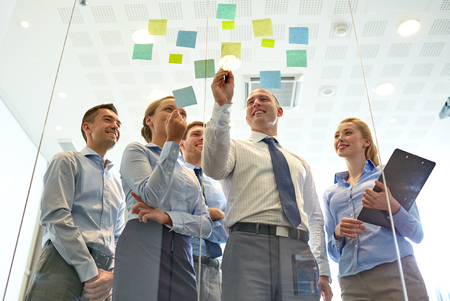 tormenta de ideas: negocios, personas, trabajo en equipo y la planificación concepto - sonriendo equipo de negocios con marcador y pegatinas que trabaja en oficina