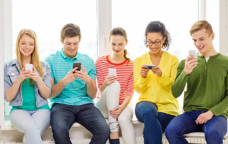 text: education, school and technology concept - smiling students with smartphone texting at school Stock Photo