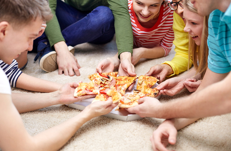 fastfood: food, leisure and friendship concept - close up of happy teenage friends eating pizza at home