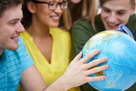 human geography: education, geography subject, high school, teamwork and people concept - group of smiling students looking at globe
