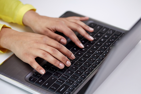 social networking: business, technology, school, people and education concept - close up of african american businesswoman or student girl hands with laptop computer sitting at table