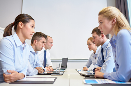 confrontation: business, people, crisis and confrontation concept - smiling business team sitting on opposite sides in office