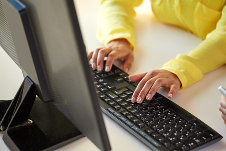 distance: business, technology, school, people and education concept - close up of african american businesswoman or student girl hands with computer sitting at table