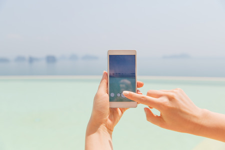 hand pointing: technology, travel, tourism, communication and people concept - close up of male hand holding smartphone on summer beach