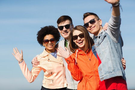 students group: friendship, tourism, travel and people concept - group of happy teenage friends in sunglasses hugging and waving hands outdoors