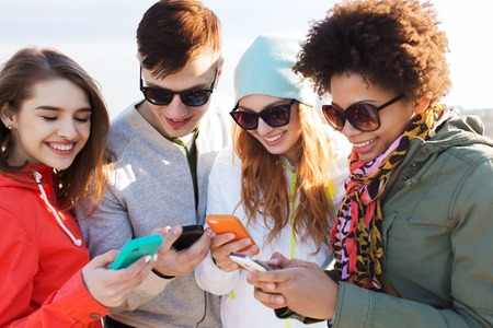 people, friendship, cloud computing and technology concept - group of smiling teenage friends with smartphone outdoors