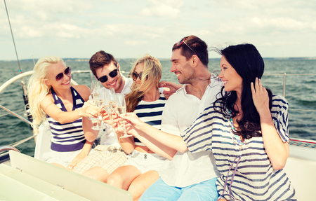 party wine: vacation, travel, sea, friendship and people concept - smiling friends with glasses of champagne on yacht