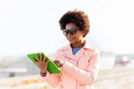 teenage girl: technology, lifestyle and people concept - smiling african american young woman or teenage girl with tablet pc computer outdoors