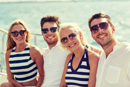 cruise travel: vacation, travel, sea, friendship and people concept - smiling friends sitting and talking on yacht deck