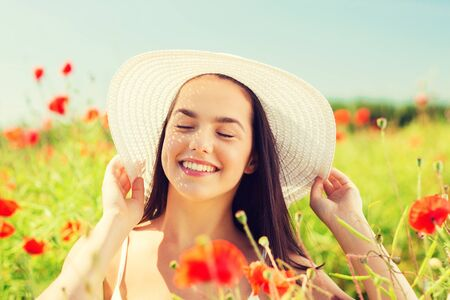 carefree: happiness, nature, summer, vacation and people concept - smiling young woman wearing straw hat on poppy field