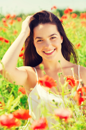 carefree: happiness, nature, summer, vacation and people concept - smiling young woman on poppy field