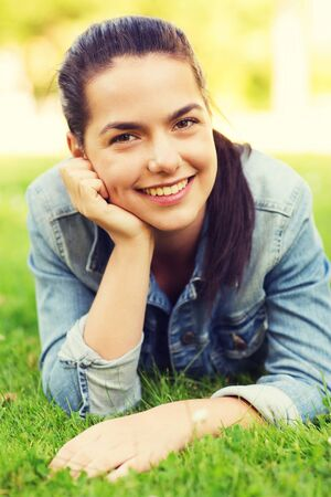 hands on head: lifestyle, summer vacation, leisure and people concept - smiling young girl lying on grass in park Stock Photo