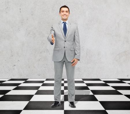 business partnership: business, people, gesture, partnership and greeting concept - happy smiling businessman in suit shaking hand standing on checkerboard pattern floor over gray background Stock Photo
