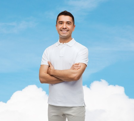 background person: happiness and people concept - smiling man in white t-shirt with crossed arms over blue sky and cloud background Stock Photo