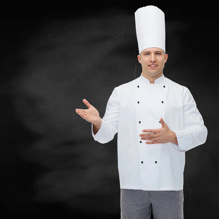 inviting: cooking, profession and people concept - happy male chef cook inviting over black chalk board background
