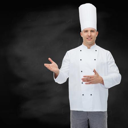 invitando: la cocina, la profesi�n y el concepto de la gente - cocinero de sexo masculino feliz cocinar invitando sobre fondo negro tarjeta de tiza