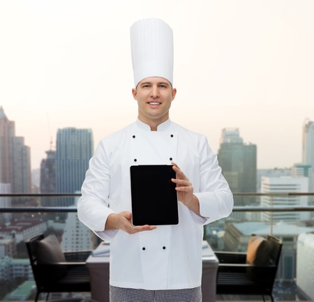 open air: cooking, profession and people concept - happy male chef cook showing tablet pc computer black blank screen over city restaurant lounge background Stock Photo