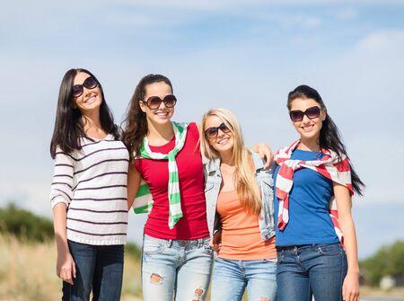 chicas adolescentes: vacaciones de verano, vacaciones y la gente concepto - adolescentes felices en gafas de sol o mujeres jóvenes se divierten en la playa