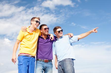uomo felice: amicizia, le vacanze estive, le vacanze e la gente il concetto - gruppo di amici sorridenti in occhiali da sole maschili che punta il dito sulla spiaggia