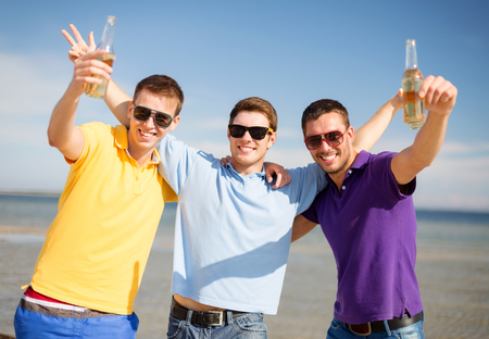 party friends: summer holidays, vacation, people and bachelor party concept - group of happy male friends having fun and drinking beer on beach