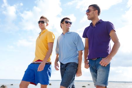 우정, 여름 휴가, 휴일 및 사람들 개념 - 해변을 따라 산책 선글라스 남자 친구 미소의 그룹