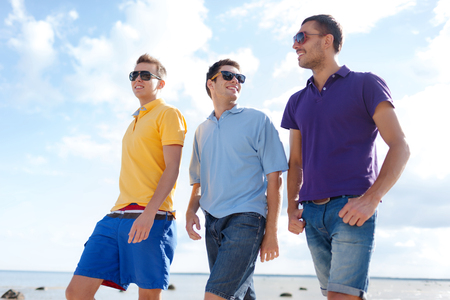 three persons: friendship, summer vacation, holidays and people concept - group of smiling male friends in sunglasses walking along beach