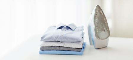 folded clothes: ironing, clothes, housework and objects concept - close up of iron and clothes on table at home